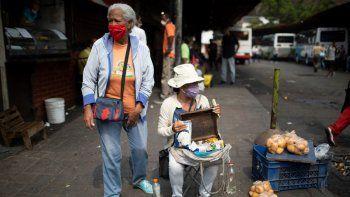 Vendedores callejeros usan mascarillas para protegerse del nuevo coronavirus mientras esperan clientes en Caracas, Venezuela, el martes 21 de abril de 2020.