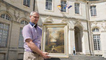 Philippe Hansch director del Centro Mundial de la Paz de Verdun muestra un cuadro del pintor francés Nicolas Rousseau que Francia recuperó.