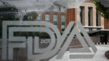 En esta imagen de archivo del jueves 2 de agosto de 2018, el edificio de la Administración estadounidense de Alimentos y Medicamentos (FDA, por sus siglas en inglés) se ve a través de mamparas con el logo de la institución en una parada de autobús en el campus de la agencia en Silver Spring, Maryland, Estados Unidos.