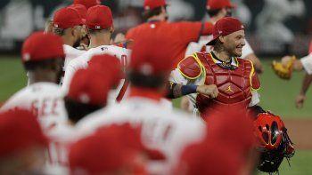 El cátcher de los Cardenales Yadier Molina (con pechera) festeja una victoria 5-4 sobre los Piratas en San Luis el 24 de julio del 2020. Los equipos de las grandes ligas están realizando rastreos internos para evitar la propagación del coronavirus. Los Cardenales, no obstante, tienen varios infectados.