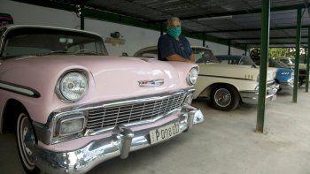 Julio Álvarez posa para una foto con sus automóviles americanos antiguos que los turistas usan para pasear por La Habana, Cuba, el viernes 24 de abril de 2020. Como sólo se permiten actividades esenciales por la cuarentena para contener la propagación del nuevo coronavirus, los autos de Álvarez están estacionados, los turistas han desaparecido y sus conductores permanecen en casa.