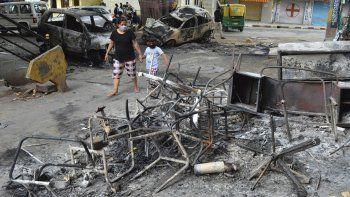 Una mujer y un niño pasan junto a los restos de vehículos y muebles quemados en protestas en Bengaluru, India, el miércoles 12 de agosto de 2020. Al menos tres personas murieron en la ciudad en choques entre la policía y manifestantes que protestaban por una publicación de Facebook que consideraban como una ofensa al islam.