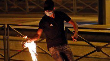 Un manifestante palestino lanza un cóctel molotov durante los enfrentamientos con las fuerzas israelíes en el campamento de Shuafat para refugiados palestinos, vecino al asentamiento israelí de Ramat Shlomo, en el este de Jerusalén anexado por Israel el 14 de mayo de 2021.