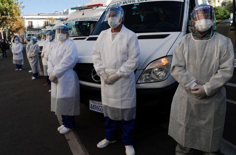Trabajadores de la salud permanecen vestidos con ropa de protección completa durante una inspección en La Paz