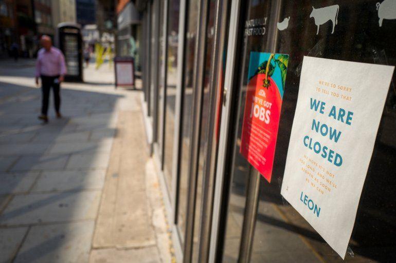 Un letrero en la ventana de un punto de venta de alimentos de León alerta a los clientes que la tienda ha cerrado temporalmente debido al COVID-19