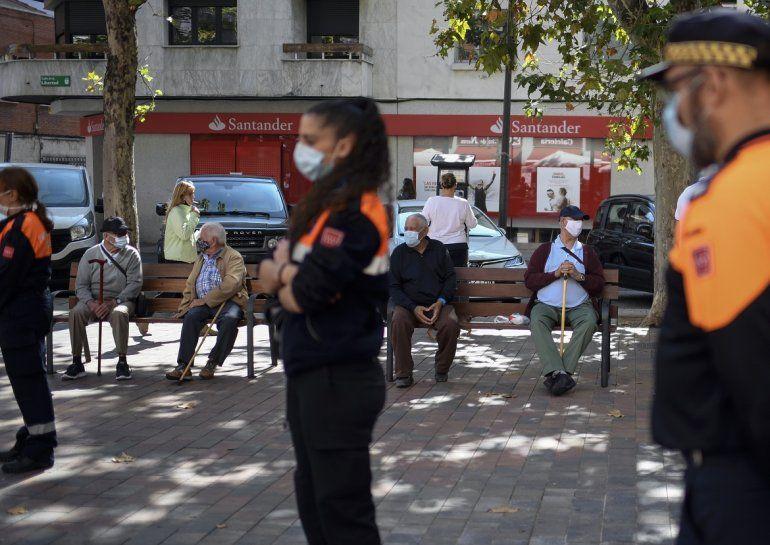 Algunos vecinos se sientan en un banco mientras los miembros de la Defensa Civil informan a los vecinos sobre las nuevas restricciones impuestas en el barrio bajo el cierre parcial de Usera