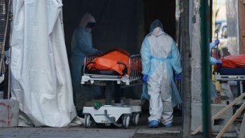 Personal de salud trasladaun cuerpoa un camión frigorífico que sirve como depósito temporal de cadáveres en el Hospital Wyckoff en Brooklyn, Nueva York.
