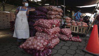 En esta foto del martes 16 de junio en la capital de El Salvador, un vendedor de verduras espera a los clientes en el mercado de La Tiendona días después de una reapertura luego de tres meses de confinamiento para contener la propagación del coronavirus.