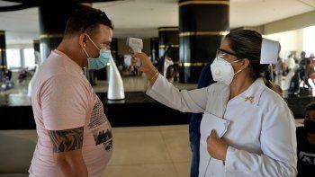 Personal médico revisa la temperatura de los turistas en el Hotel Internacional Varadero, provincia de Matanzas, el 23 de octubre de 2020. Varadero, el balneario más importante de Cuba, reabre al turismo internacional, en medio de la pandemia del coronavirus.