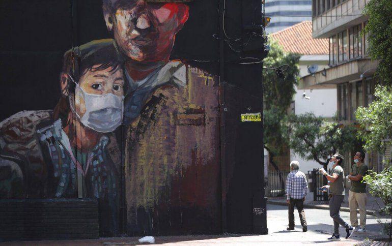 Un mural pintado recientemente muestra a un joven usando una máscara durante una cuarentena ordenada por el gobierno para evitar contagios por el nuevo coronavirus en Bogotá