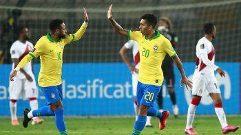 El brasileño Roberto Firmino (der.) celebra con su compañero Neymar durante un partido de fútbol clasificatorio sudamericano para la Copa Mundial de la FIFA 2022.