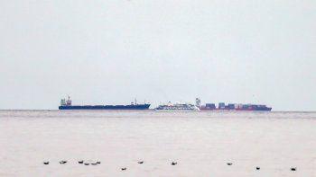 El crucero australiano Greg Mortimer, al centro, es rodeado por dos buques de carga frente al puerto de Montevideo, Uruguay, el domingo 5 de abril de 2020. De 217 personas entre pasajeros y tripulantes sometidos a pruebas a bordo del crucero, 128 dieron positivos por coronavirus, según Aurora Expeditions, organizadora del viaje.