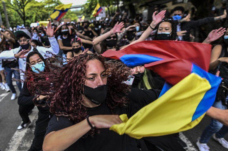 Los manifestantes bailan durante una protesta contra un proyecto de ley de reforma tributaria lanzado por el presidente Iván Duque