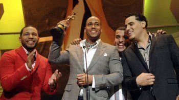 Romeo Santos, segundo de izquierda a derecha, levanta su estatuilla mientras Henry, izquierda, Mikey, derecha, y Lenny del grupo de bachata Aventura lo miran tras recibir El Soberano en los premios Cassandra de República Dominicana en el Teatro National de Santo Domingo, el martes 16 de marzo de 2010.