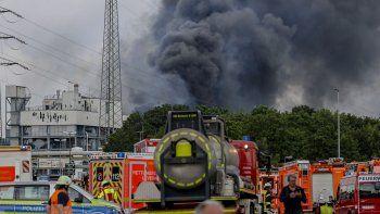 Vehículos de emergencias de bomberos, rescatistas y policías estacionados cerca del acceso al recinto industrial Chempark, sobre el que se alza una negra humareda, en Leverkusen, Alemania, el martes 27 de julio de 2021.