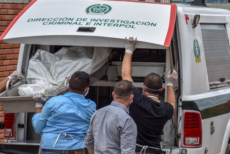 Policías descargan los cadáveres de víctimas de una masacre presuntamente a manos de grupos armados en el municipio colombiano de Arauca