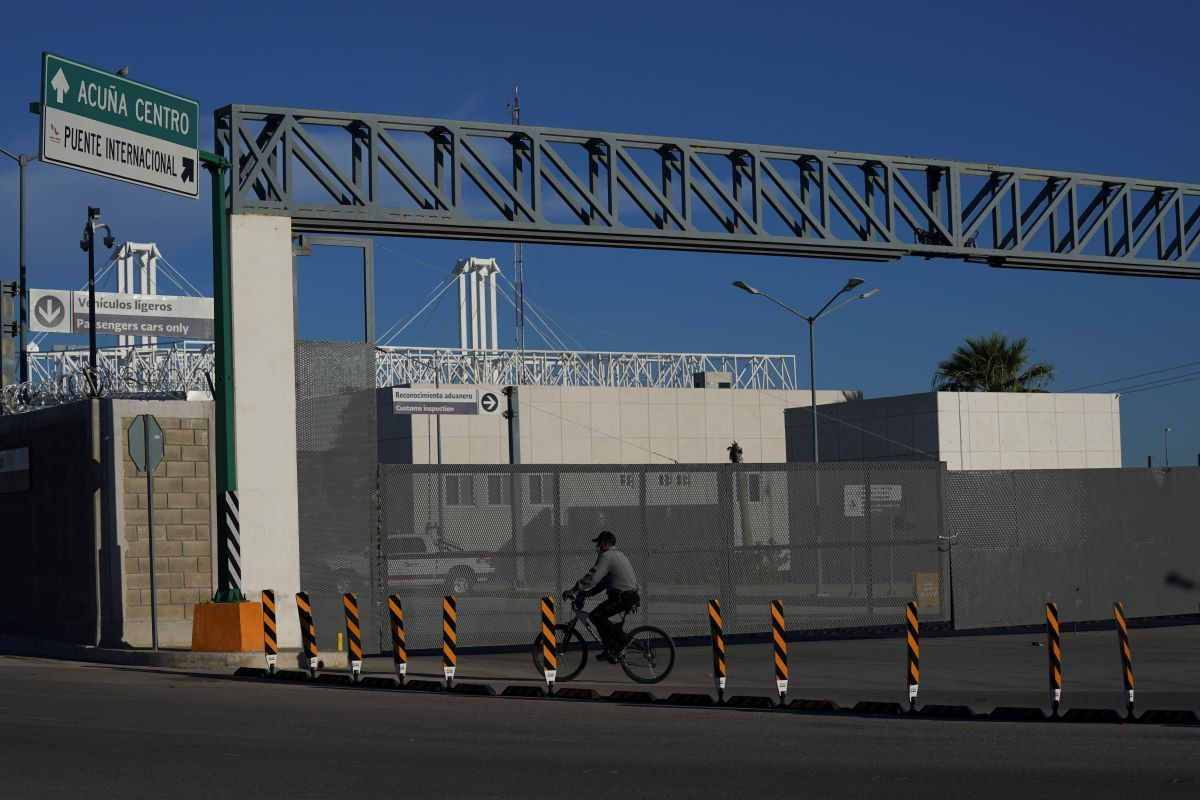 Un hombre en bicicleta frente a la entrada cerrada de un puente fronterizo internacional que conecta a las ciudades de Del Río, Texas, y Ciudad Acuña, México, el viernes 24 de septiembre de 2021.