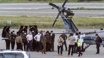 El presidente de Colombia, Iván Duque (izq.), Camina rodeado de guardaespaldas cerca del helicóptero presidencial en la pista del Aeropuerto Internacional Camilo Daza luego de que fuera alcanzado por disparos en Cúcuta, Colombia, el 25 de junio de 2021.
