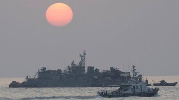 En esta imagen de archivo, tomada el 22 de diciembre de 2010, un barco del gobierno navega junto a una base naval flotante surcoreana al amanecer, cerca de la isla de Yeonpyeong, en Corea del Sur.