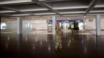 Un miembro de la Guardia Nacional puertorriqueña vigila una entrada del Aeropuerto Luis Muñoz Marín, donde se instalaron estaciones de monitoreo para detectar posibles casos del nuevo coronavirus entre los pasajeros, en Carolina, Puerto Rico, el lunes 16 de marzo de 2020.