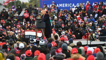 Partidarios escuchan al presidente Donald Trump mientras habla en un mitin Make America Great Again en el Aeropuerto Internacional del Condado de Oakland, el 30 de octubre de 2020, en Waterford Township, Michigan.