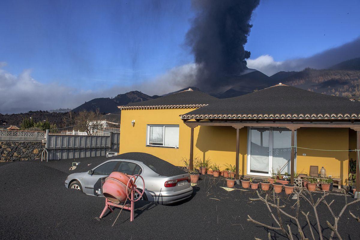 Una capa de ceniza volcánica cubre una casa, un automóvil y sus alrededores mientras en el fondo un volcán sigue en erupción en la isla canaria de La Palma, España, el lunes 4 de octubre de 2021.