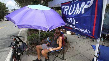 Ray Renaud, de Daytona Beach, Florida, se cubre con una sombrilla mientras simpatizantes del presidente Donald Trump acampan frente al Amway Center el lunes 17 de junio de 2019, antes de un evento para dar inicio a la campaña de reelección 2020 en Orlando, Florida.