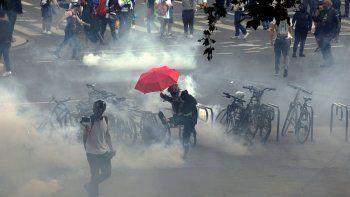 Un manifestante lanza un proyectil de gas lacrimógeno humeante durante un día nacional de protesta contra la vacunación obligatoria Covid-19 para ciertos trabajadores y el uso obligatorio del pase de salud solicitado por el gobierno francés en París el 31 de julio de 2021.