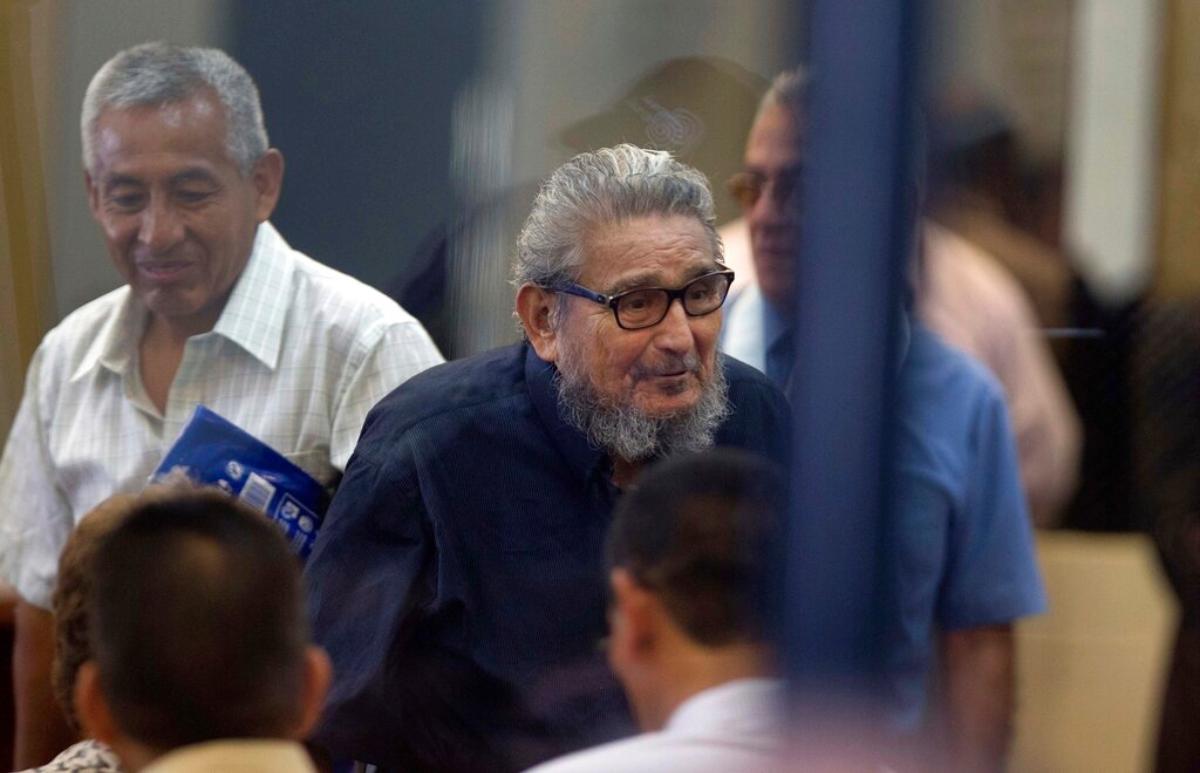 Abimael Guzman, fundador y líder del movimiento guerrillero Sendero Luminoso (al centro), mientras ingresa a la sala de un tribunal en la Base Naval de Callao, Perú.