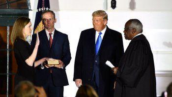 El presidente Donald Trump observa cómo el magistrado de la Corte Suprema, Clarence Thomas (derecha), jura a la jueza Amy Coney Barrett como juez de la Corte Suprema de Estados Unidos, flanqueada por su esposo Jesse M. Barrett, durante una ceremonia en el jardín sur de la Casa Blanca el 26 de octubre de 2020 en Washington, DC.