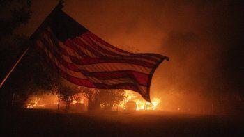 Una bandera estadounidense ondea en el viento frente a una casa en llamas en Vacaville, California, durante el incendio del Complejo Relámpago LNU el 19 de agosto de 2020.