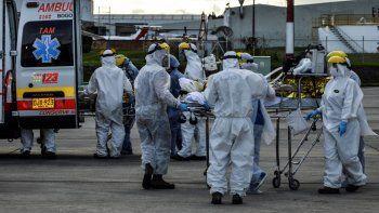 Trabajadores de la salud trasladan desde un avión a la ambulancia a personas heridas en una explosión. Un avión de la Fuerza Aérea de Colombia los transportó desde el norte de Colombia a Bogotá, el 8 de julio de 2020.