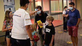 Los pasajeros que lleven máscaras protectoras en la boca y la nariz verán su temperatura como parte de los controles de seguridad sanitaria por parte de un miembro de la tripulación mientras abordan el crucero MSC Grandiosa antes de zarpar desde la ciudad portuaria noroccidental de Génova el 16 de agosto de 2020.
