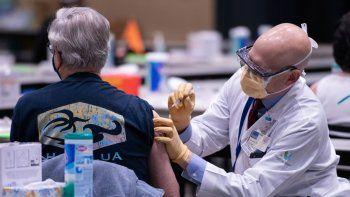 El director clínico John Corman administra a una persona de la tercera edad,una dosis de la vacuna Pfizer COVID-19 en el centro de Seattle, Washington, el 24 de enero de 2021.