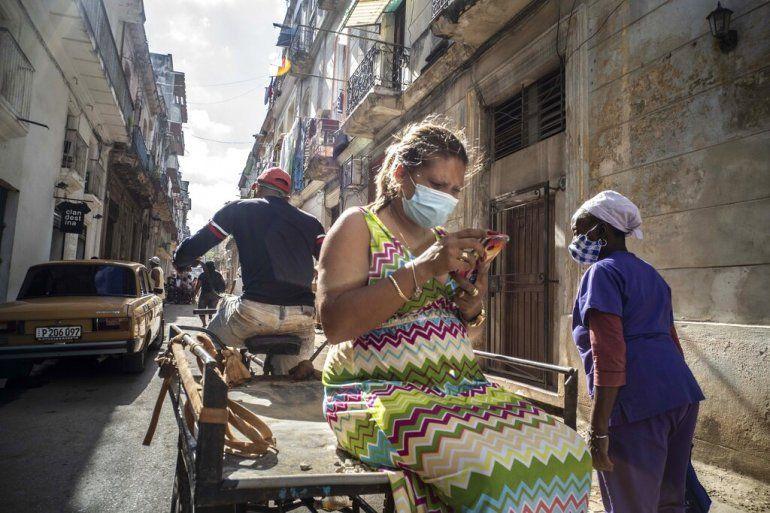 Una mujer que usa una máscara para frenar la propagación del nuevo coronavirus mira su teléfono móvil mientras viaja en un carrito de bicicleta en La Habana