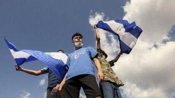 Tres jóvenes ondean banderas nacionales durante una protesta para exigir que el gobierno libere a cientos de manifestantes detenidos, en Managua, Nicaragua, el sábado 16 de marzo de 2019