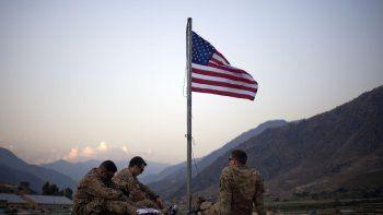 En esta imagen de archivo del 11 de septiembre de 2011, soldados estadounidenses sentados bajo una bandera estadounidense recién izada para conmemorar el 10mo aniversario de los ataques del 11 de septiembre de 2001, en la Base Operativa Bostick, en la provincia de Kunar, Afganistán.