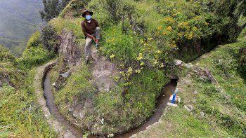 Foto de la hoja publicada por la organización Aquafondo de un campesino sentado junto a parte de una red prehispánica de canales de piedra que surca las laderas de los cerros que transportan agua para la agricultura, en San Pedro de Casta, provincia de Lima, Perú, el 18 de abril. 2021.