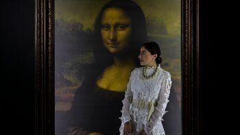 Una mujer posa para fotografías junto a una reproducción del retrato de Lisa Gherardini, esposa de Francesco del Giocondo, conocida como la Mona Lisa o La Gioconda, durante la exposición Da Vinci Experience en la Ciudad de México, el 10 de junio de 2021.
