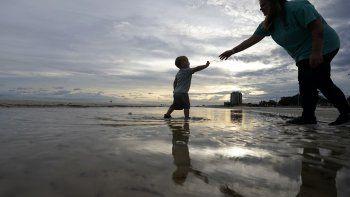 Nikita Pero de Gulfport, Mississippi, camina con su hijo Vinny Pero, de 2 años, por la playa en el Golfo de México, en Biloxi, Mississippi, el lunes 14 de septiembre de 2020.
