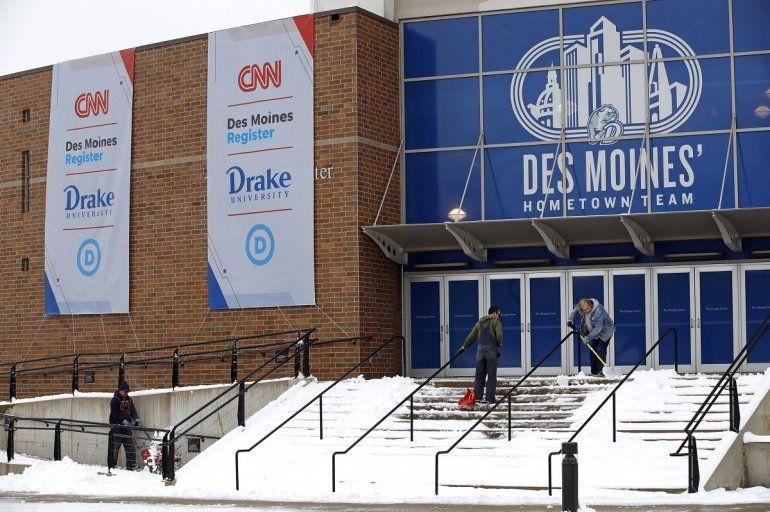 Trabajadores despejan la nieve frente a un salón en la Universidad Drake