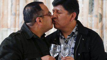 Guido Montaño, a la izquierda, y David Aruquipa se besan para una foto durante una conferencia de prensa en La Paz, Bolivia, el viernes 11 de diciembre de 2020. Después de años de batallas en los tribunales, la pareja registró legalmente su unión civil, la primera en lograr ese reconocimiento en Bolivia.
