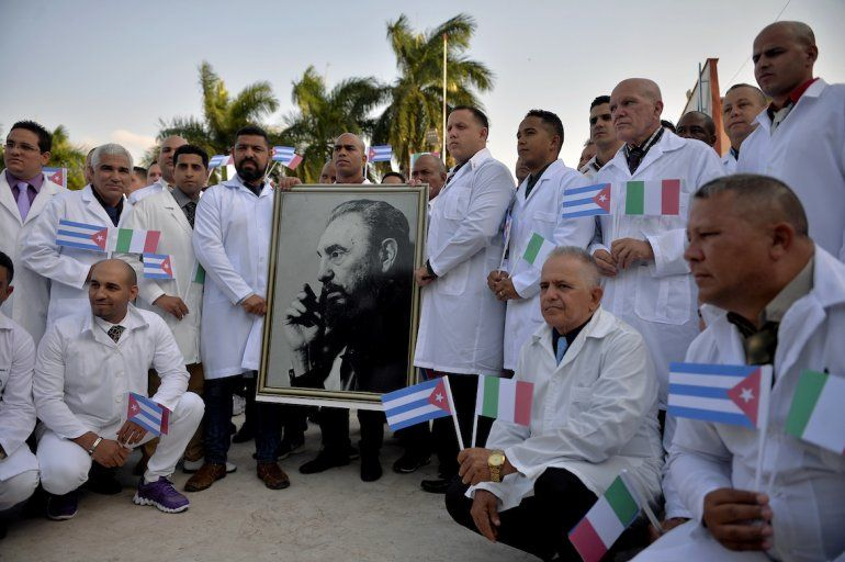Médicos y enfermeras de la Brigada Médica Internacional Henry Reeve de Cuba posan con un retrato del difunto líder cubano Fidel Castro mientras se despiden antes de viajar a Italia para ayudar en la lucha contra la pandemia del coronavirus COVID-19
