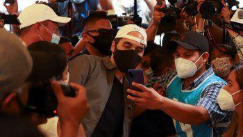 El presidente Nayib Bukele posa para una selfie con un trabajador electoral, mientras vota en las elecciones locales y legislativas en un colegio electoral en San Salvador, El Salvador, el domingo 28 de febrero de 2021.