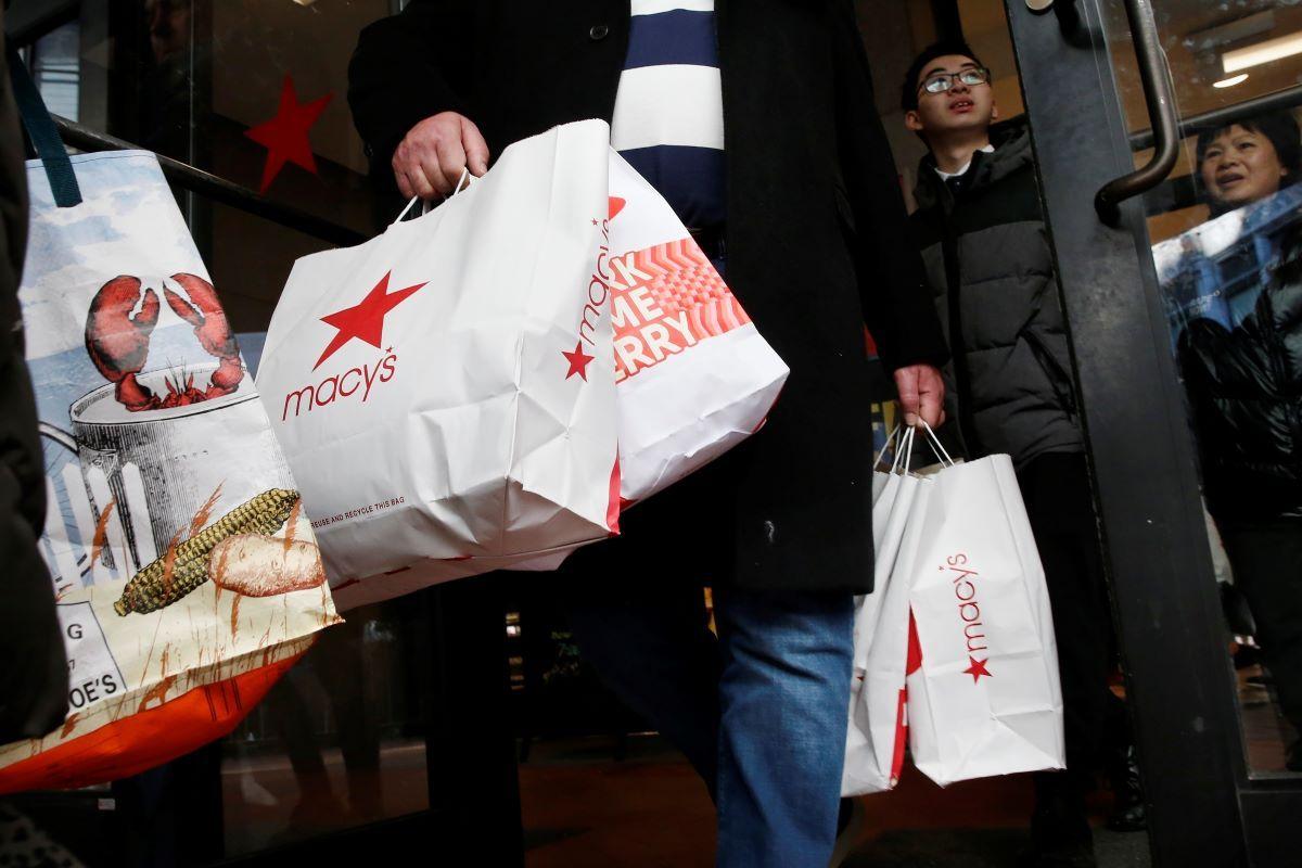 Varias personas salden de una tienda Macys con sus compras.