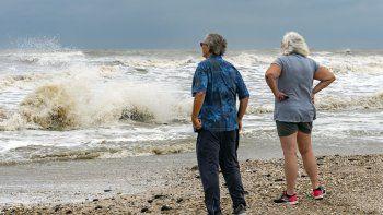 Steve y Linda Buser, de Beaumont, miran el fuerte oleaje en la playa junto al cruce entre la autopista 124 y la 87 en la Península de Bolívar, Texas, el domingo 20 de septiembre de 2020. Se esperaba que la tormenta tropical Beta llevara esta semana fuertes lluvias a la costa de Texas y Luisiana.