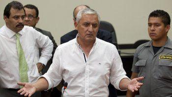 En esta foto de archivo del 28 de marzo de 2016, el presidente guatemalteco Otto Pérez Molina, al centro, habla con la prensa después de asistir a una audiencia en una corte en Ciudad de Guatemala.