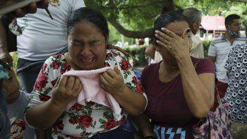 Mujeres lloran mientras explican que tres de sus familiares fueron asesinados el día anterior en El Ripial, estado Apure, Venezuela, luego de cruzar el río hacia Arauquita, Colombia, el viernes 26 de marzo de 2021.