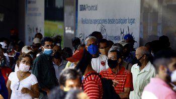 Personas esperan en la puerta de una entidad bancaria en Valencia, Venezuela, en medio de la pandemia de COVID-19. El régimen y la oposición acordaron un plan para enfrentar la pandemia, con la mediación de la OPS.