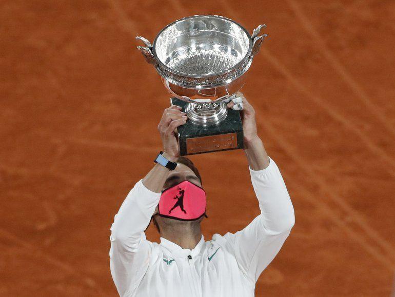 El español Rafael Nadal sostiene el trofeo mientras celebra ganar el partido final del torneo de tenis Abierto de Francia contra el serbio Novak Djokovic en tres sets